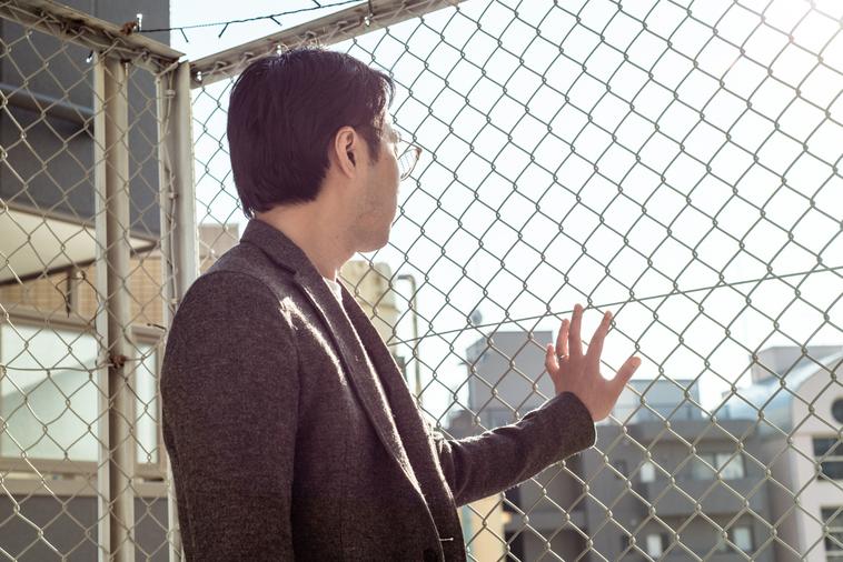 【写真】金網のフェンスを見つめているまつうらさんの背中姿