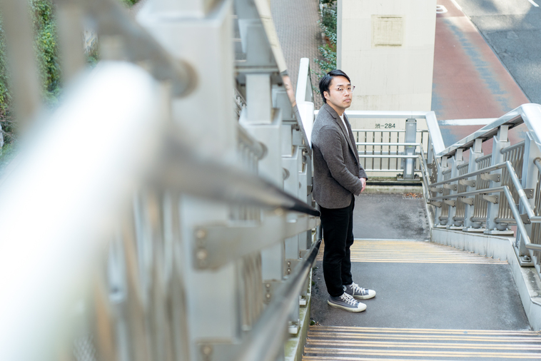 【写真】歩道橋の階段に立ち、こちらを見るまつうらさん